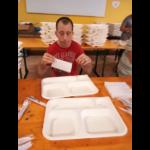 Una persona con disabilità che aiuta nella mensa dell'Oratorio San Luigi