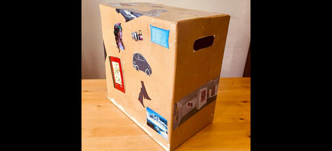 Nella foto c'è una scatola di cartone decorata con immagini di giornali a colori. Si chiama Box l-inc