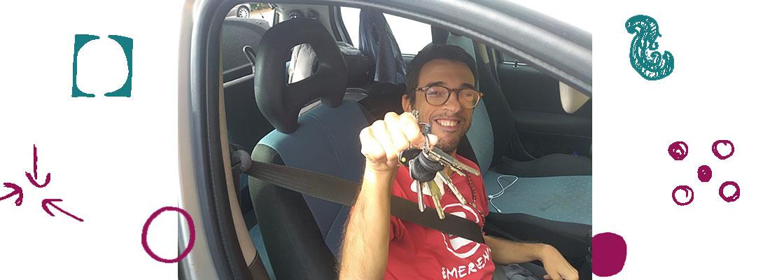Un ragazzo sorride e tiene in mano un mazzo di chiavi della macchina